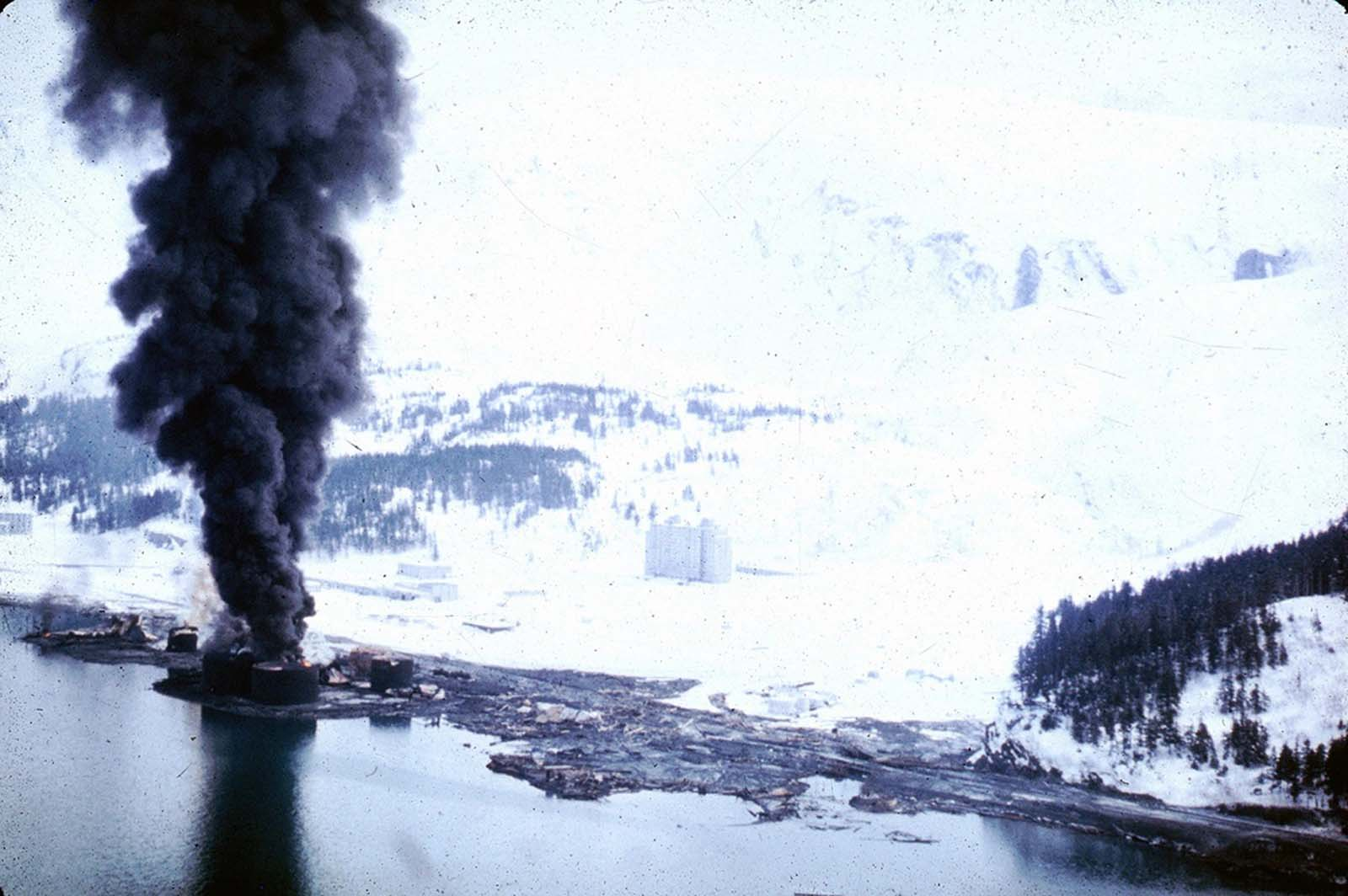 The dock area, a tank farm, and railroad facilities in Whittier, Alaska were severely damaged by surge-waves developed by underwater landslides in Passage Canal, on March 27, 1964. The waves inundated the area of darkened ground, where the snow was soiled or removed by the waves.