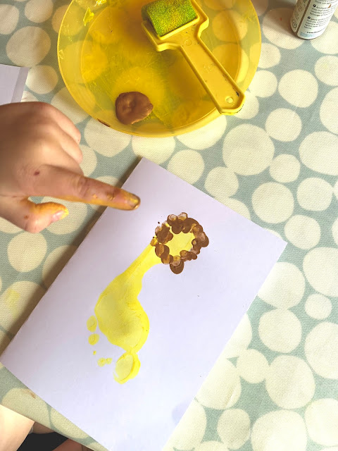 Toddler fingers putting a finger print mane on a yellow footprint lion