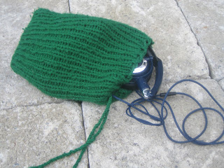 Image of a knitted ribbed bag made of green yarn, laying open with a pair of headphones half-out