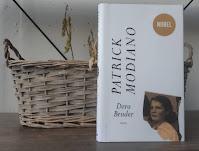 Dora Bruder -kirja nojaa parvekelaatikkoon, jossa on kuihtuneita kasveja