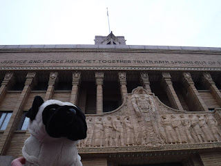 "a plush pug appears in front of an elaborately carved building front featuring many pillars, many carved men, and the words ""justice and peace have met together. truth hath sprung out of"" visible"