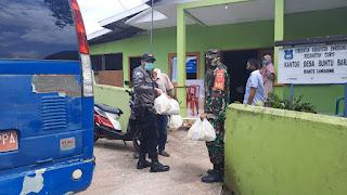 Bhabinkamtibmas Polsek Curio Bersama Babinsa Kawal Penyaluran Bantuan Sembako Dari Pemerintah