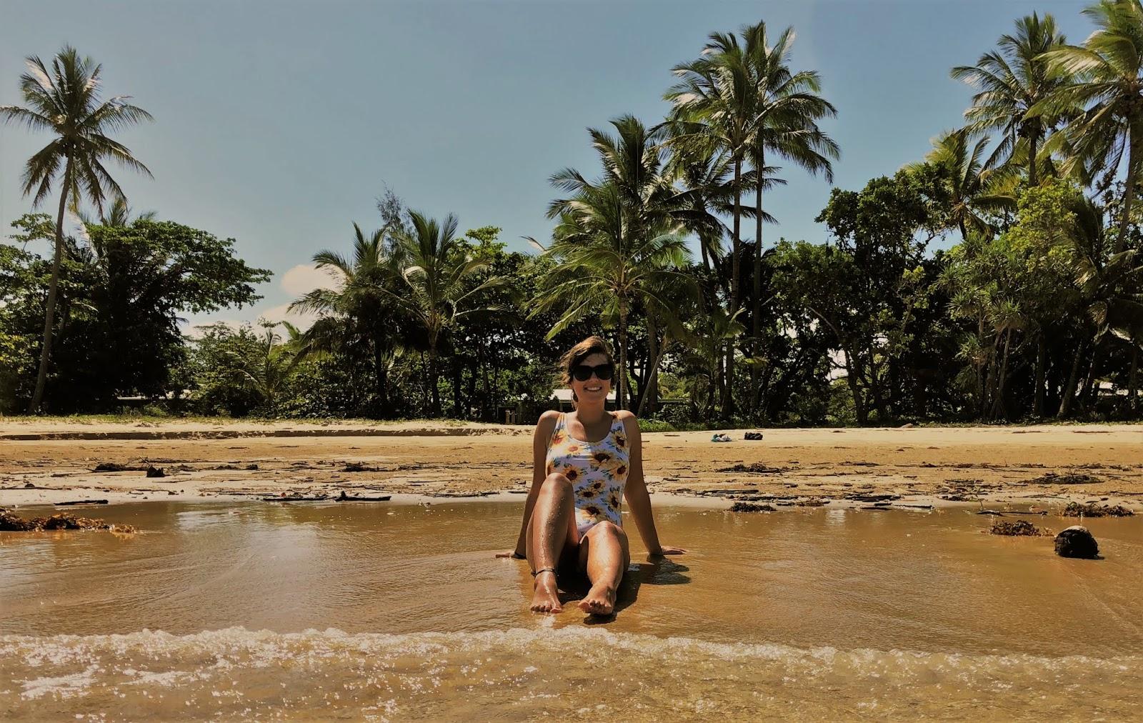 Plaża w w australijskim miasteczku Mission Beach. Zdjęcie zrobione z perspektywy Morza Koralowego. Podróżniczka sziedzi w stroju kąpielowym na piasku przy samej wodzie. Z tyłu za nią widnieją palmy i gęsty busz.