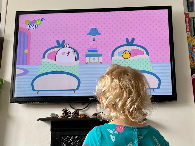 A photo of the back of a young girls head as she looks towards a TV with an episode of Molang on it