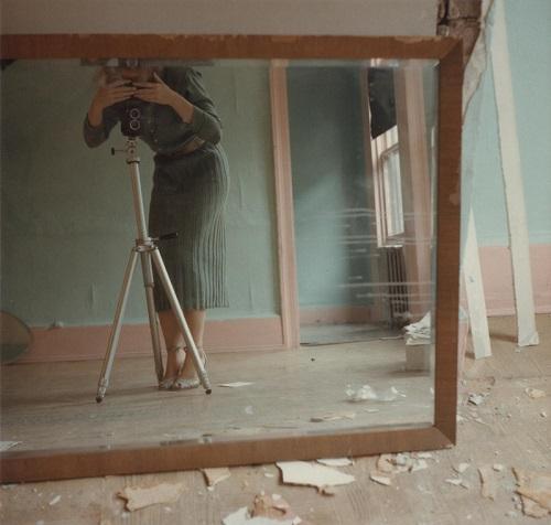 Foto vintage: una mujer se autorretrata con la ayuda de un espejo al interior de una casa. Su camara es antigua.