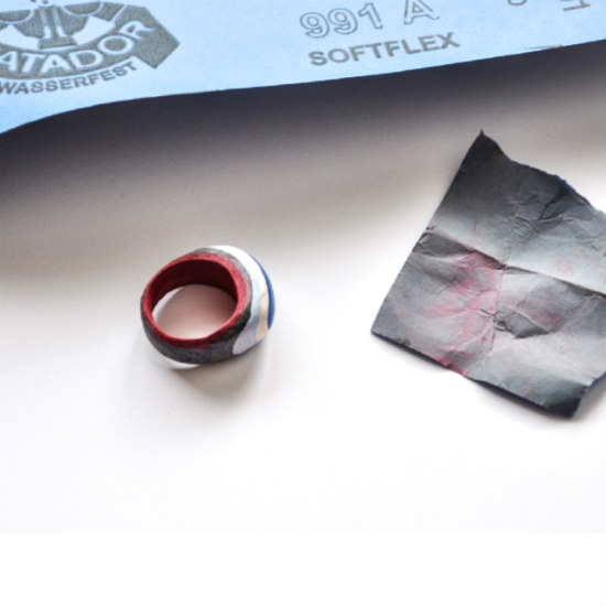 continuing to ready a layered paper ring by sanding with fine grit paper