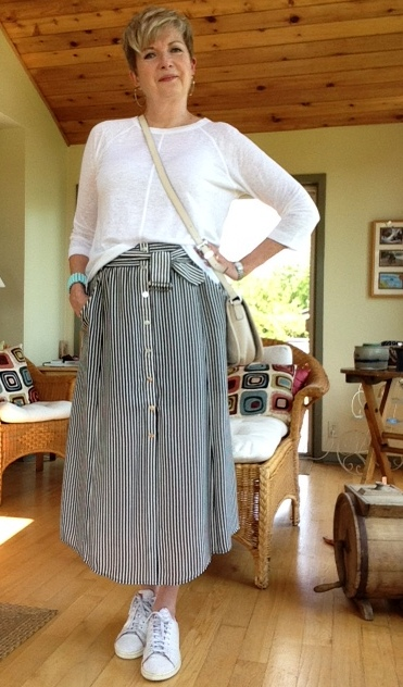 Wearing a striped long skirt with a white linen tee, and white sneakers, the tee half tucked in