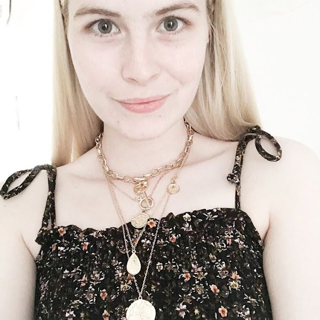 woman wearing gold necklaces