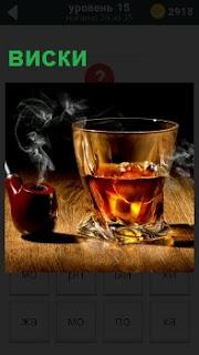 На столе стоит стакан с виски и трубка дымится, на освещенном месте
