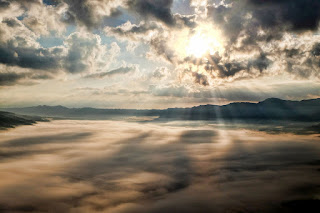 A photograph of the sky, with some landscape in the background, showing clouds above and below the viewer and the sun shining through the clouds above.