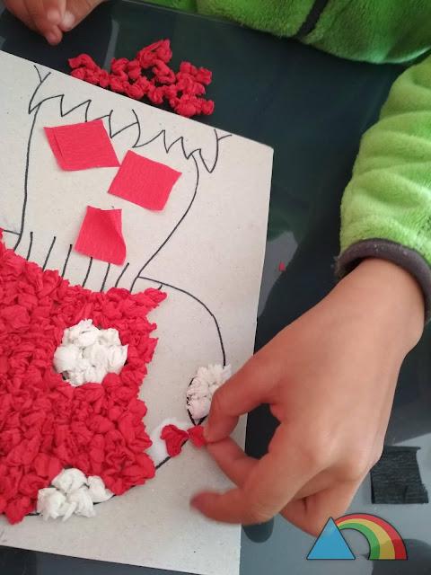 Manos de niño arrugando cuadrados de papel crepé, y pegándolos con cola blanca en un dibujo de una seta