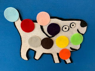 Closeup of white flannel dog covered in colorful flannel circles on flannel board