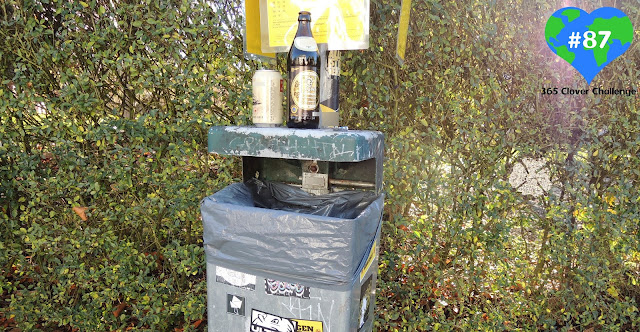 Picture of a bin with a beer bottle and can on top of it