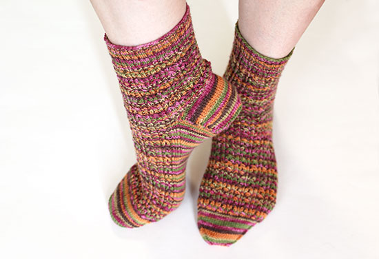 Feet wearing wool socks knit in autumn colors on a white background.