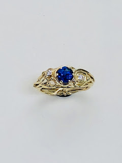 Blue stone ring with white stones on the sides, looping wires