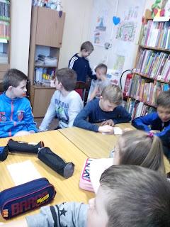 Dzieci słuchają rozdziału, jeden z chłopców próbuje dopasować uzyskane informacje do krzyżówki