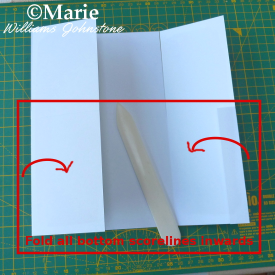 Folding scored lines inwards on boxed card design craft