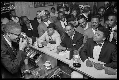 black and white photo of Malcolm X photographing Cassius Clay, in a diner in Miami, 1964