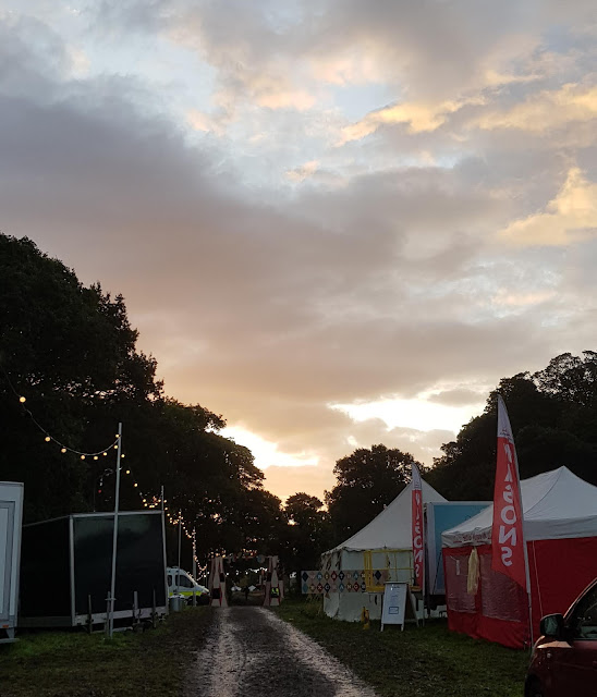 6am Saturday morning Just So Festival 2019 rain puddles, wristband exchange and cloud filled sky with pink tinge