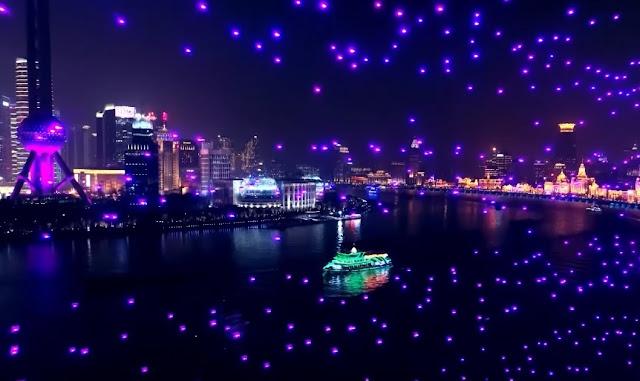 Drones subindo e fazendo milhares de focos de luzes sobre o rio