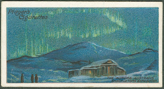 A card with an illustration of the northern lights over a snowy cabin.
