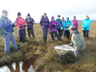 guide sitting at pond explains to group about the red grouse habitat
