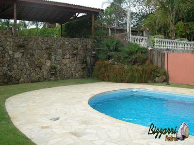 Muro de pedra rústica com a construção da piscina de vinil, o piso de pedra com caco São Tomé e a execução do paisagismo em sítio em Mairiporã-SP.