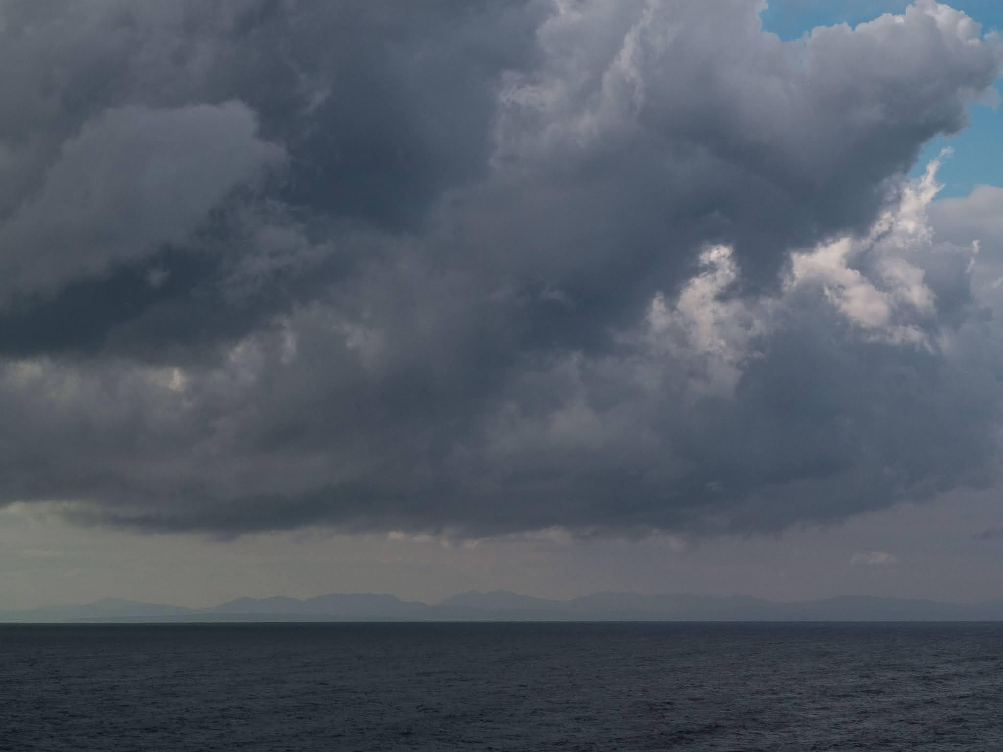 Rain clouds over a mountainous coast line on the Mediterranean Sea.