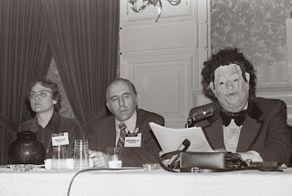 APA panel of 3 people, one wearing a full head mask of a clown