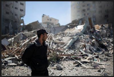 Seorang polisi Palestina berada pada  reruntuhan Jala Tower, gedung 13 lantai kantor Associated Press dan  media Al Jazeera, yang diserang melalui udara oleh Israel di Gaza pada Sabtu (15/5/2021).