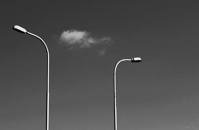 A black and white Minimalist Photo of two street lamps curved in the opposite direction split by a Minimalist White Cloud