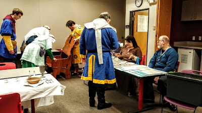 Some medieval attired people assemble a wooden chair, others seated painting awards.