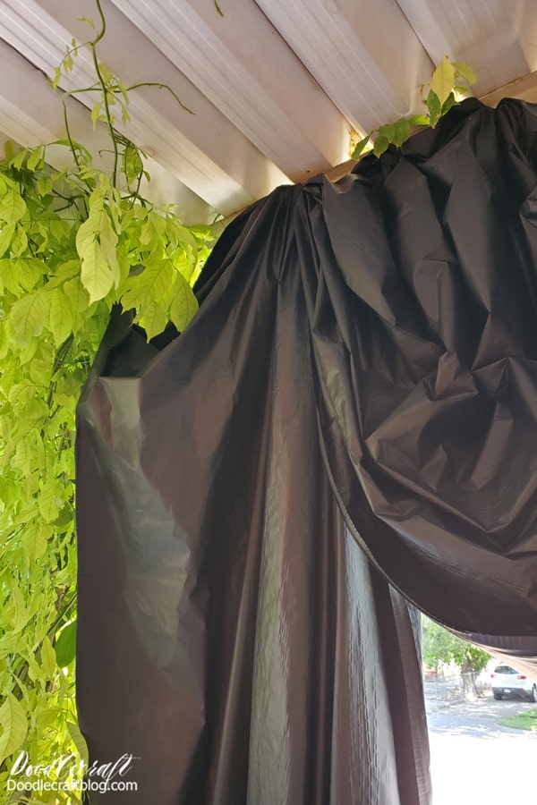 Begin by setting the backdrop for the spooky Halloween scene. I used a roll of plastic tablecloth to create a Victorian swag curtain on the front porch. This is key for hiding some surprises on the front porch. Plus, it adds to the spookiness.