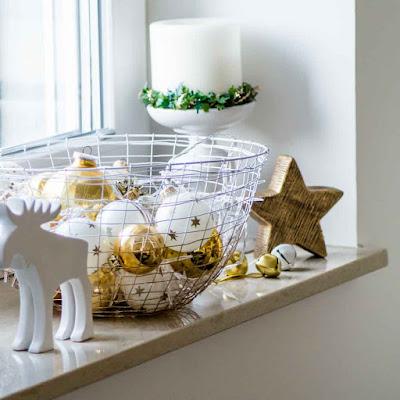 Deko an Weihnachten. Goldene Kugeln, Metallglöckchen, Rentier auf Fensterbank