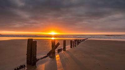 Wallpaper Sunset, Sea, Beach, Wooden pillars, Sand