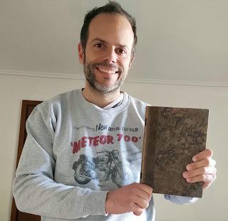 Smiling man holding Bertil Hult's book.
