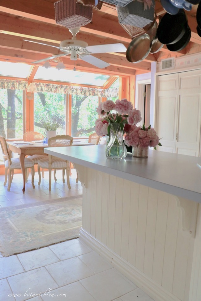 Romantic French country pink peonies on kitchen island with breakfast sunspace