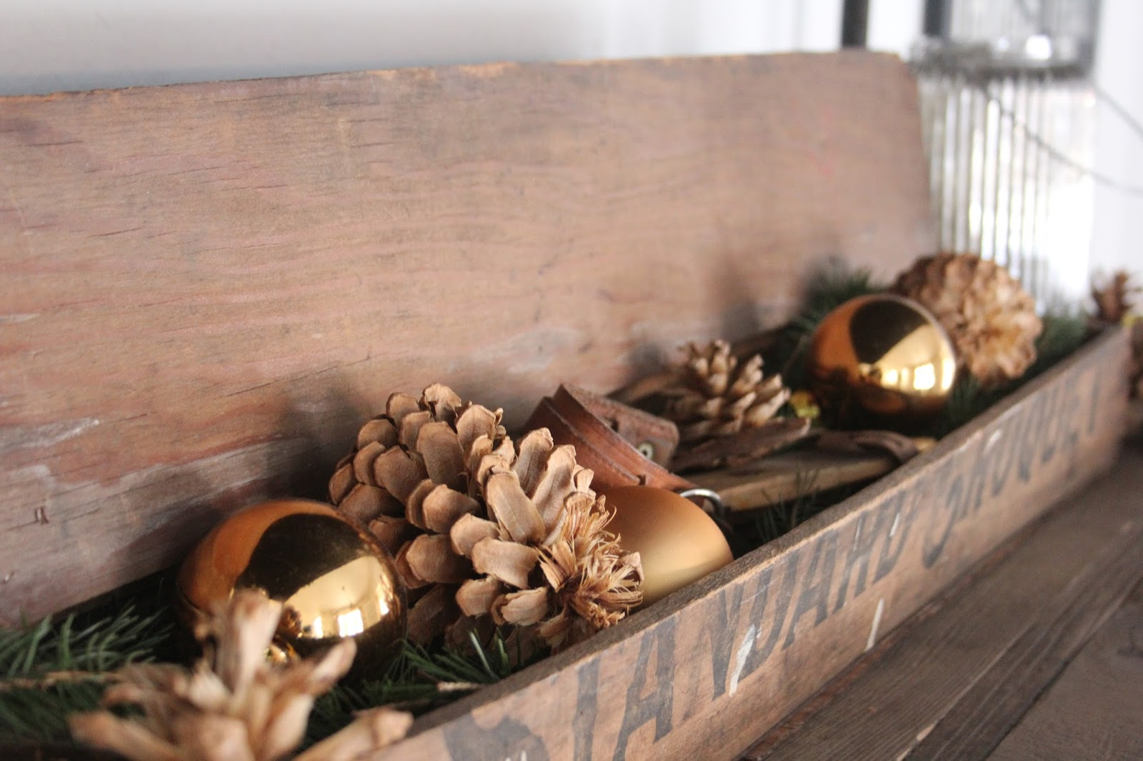 Rustic vintage box filled with pinecones, gold balls, and greenery for Christmas - Hello Lovely Studio