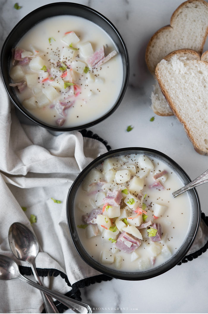 Two bowls of potato and ham soup with bread