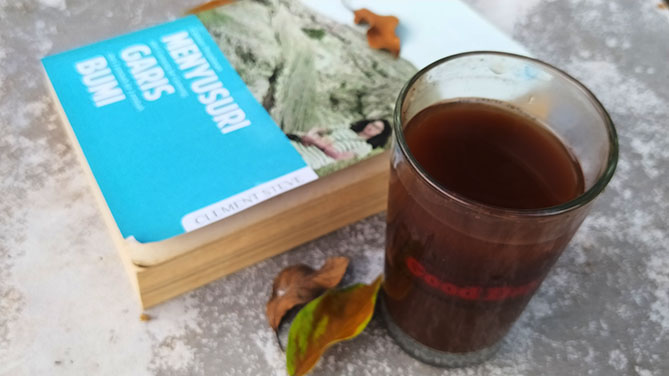 Membaca buku sembari menyesap kopi