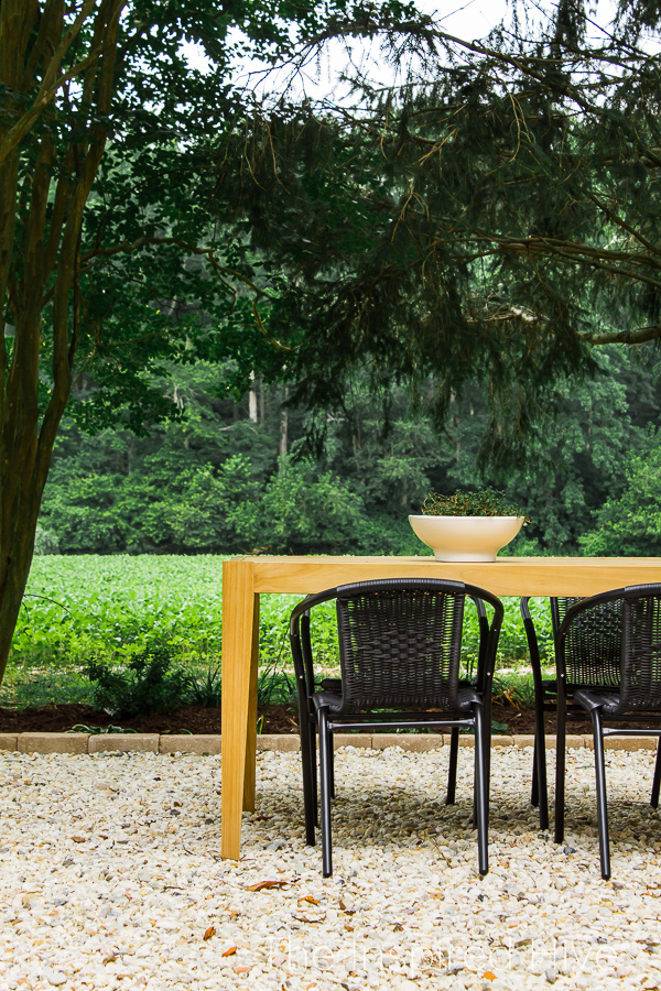 Teak outdoor dining table with black chairs
