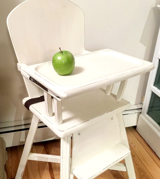 White baby high chair with green apple