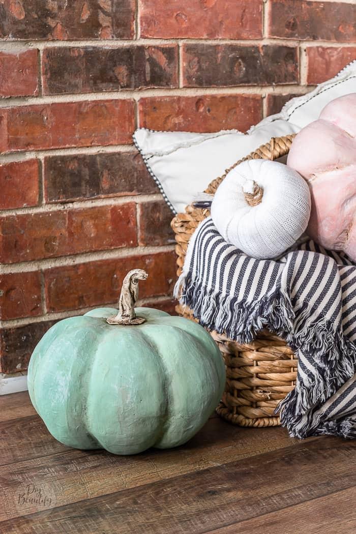brick wall, farmhouse floors and basket full of DIY heirloom Cinderella pumpkins