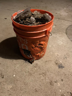 Thick orange 5 gallon bucket full of ash with lots of melt marks