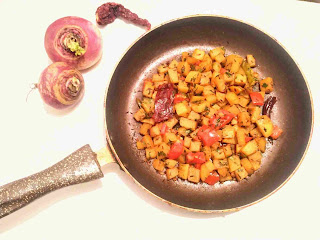 Serving spiced shalgam ( turnip) in a pan for shalgam ki sabzi, Red chilly and shalgam whole in background