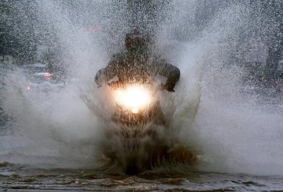 Чоловік на скутері їде через затоплену вулицю в Бангалорі, Індія