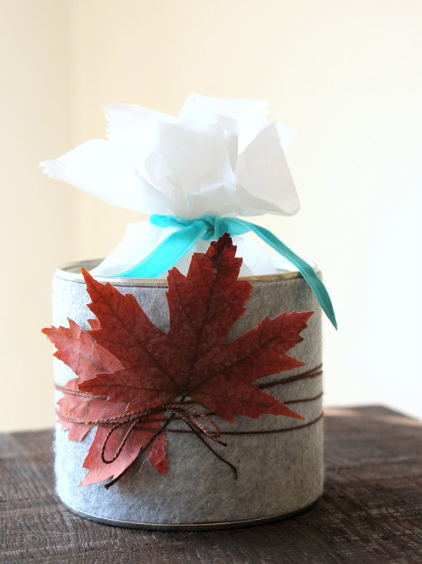 Upcycled nut tin covered in grey felt and natural leaves