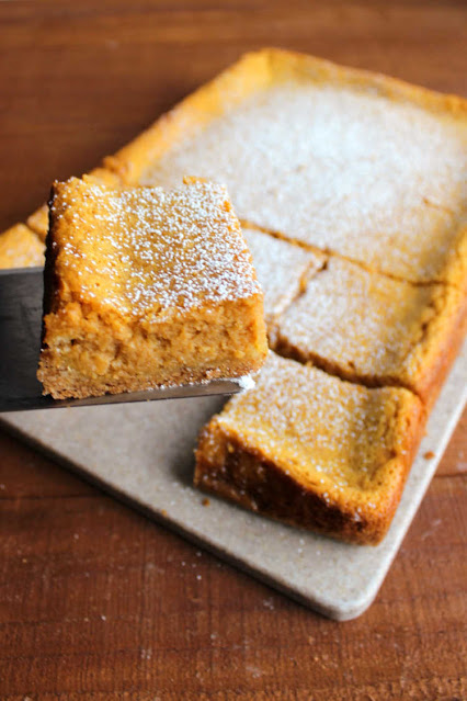 lifting slice of pumpkin gooey butter cake off of tray