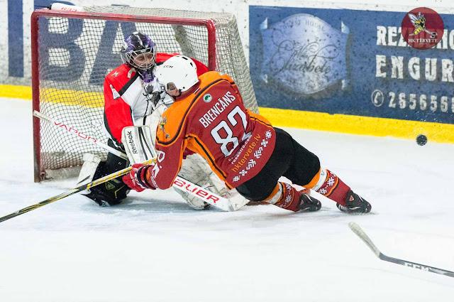 Hokejists krīt vārtsarga priekšā uz ledus
