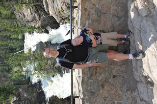 father and son in front of a waterfall
